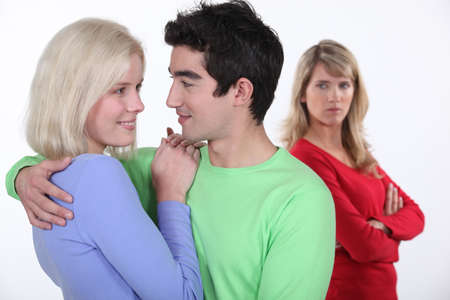 cheating woman: Jealous woman looking at a man hugging a young woman