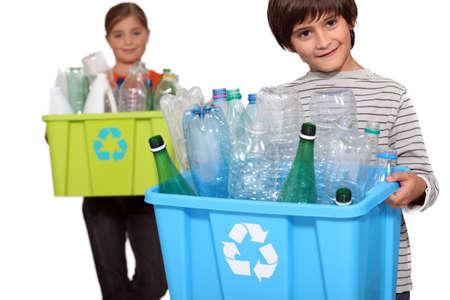 ni�os reciclando: Ni�os de reciclaje de botellas de pl�stico Foto de archivo