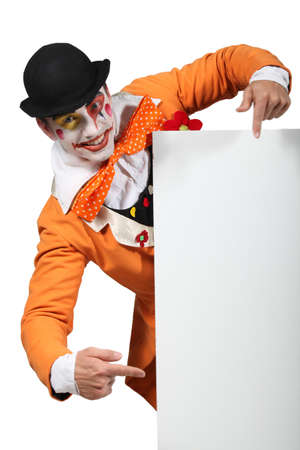clowning: Man dressed up as a joker pointing to a board left blank for your image