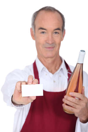 Waiter holding bottle of wine and blank business card photo
