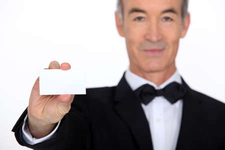 55 60 years: Silver service waiter holding up a business card