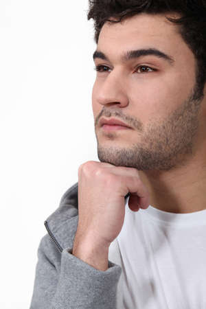 casual hooded top: Pensive man stood touching chin with fist