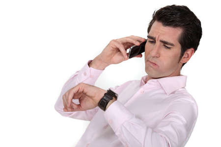 watch over: A businessman over the phone looking at his watch  Stock Photo