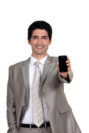 A businessman handing his phone  photo