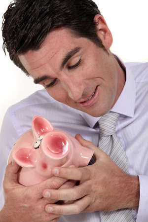 stingy: A businessman hugging his piggy bank