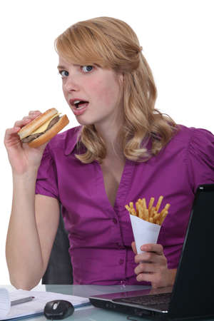 Woman eating burger and fries at desk photo