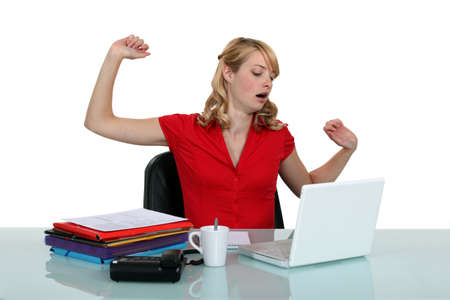 demotivated: Tired woman sitting at a laptop