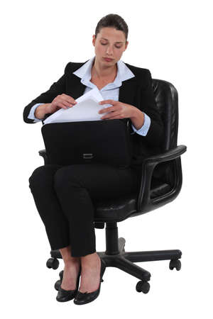 pantsuit: Businesswoman getting documents out of a briefcase Stock Photo