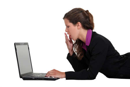 dullness: Woman yawning in front of a computer