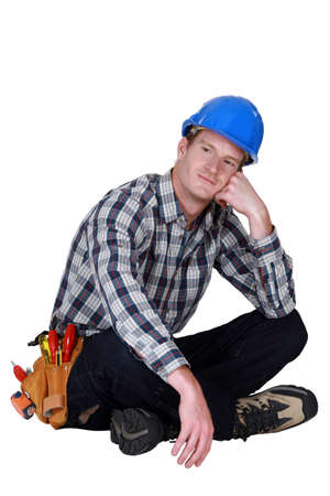 Dreamy tradesman sitting cross-legged Stock Photo - 17220035