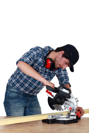miter: Man using a mitre saw
