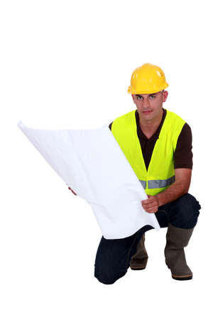 high visibility: Tradesman studying a blueprint