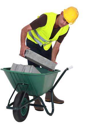 Worker putting cinderblocks in a wheelbarrow photo