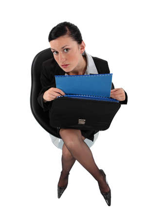 businesswoman holding a briefcase full with folders photo