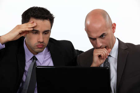 Stressed businessmen looking at laptop screen photo