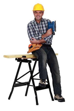 tradesperson: Tradesman sitting on a workbench