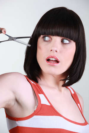 Woman scared of a pair of hairdressing scissors photo