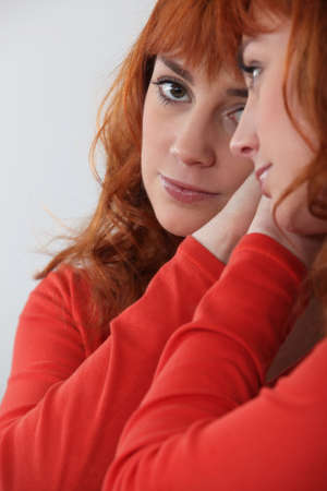 woman in the mirror: Redhead looking in a mirror
