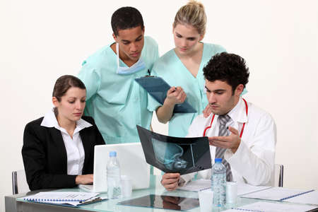young physician surrounded by male and female nurse Stock Photo - 17220197