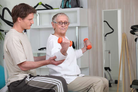 instructor: Woman working out with the help of her personal trainer Stock Photo
