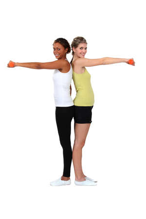 two women doing exercises with dumbbells photo