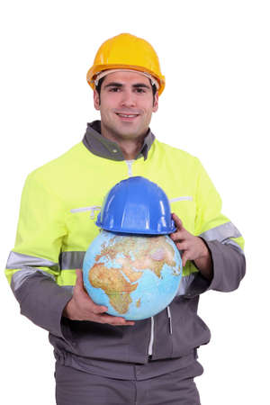 Worker putting a helmet on a globe photo