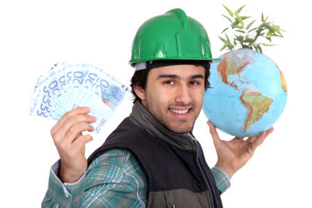 Laborer holding a globe, a green plant and twenty Euros bills photo