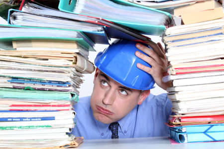 Architect surrounded by piles of paperwork photo