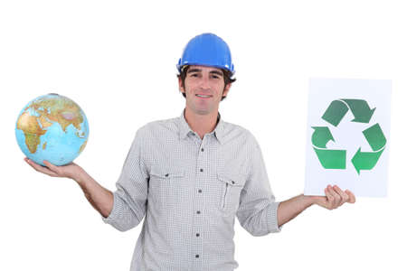 Construction worker holding a globe and recycle sign photo