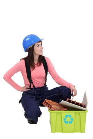 tradeswoman: Young tradeswoman squatting beside a recycling bin
