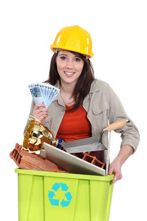 A tradeswoman holding a recycling bin and a wad of cash photo