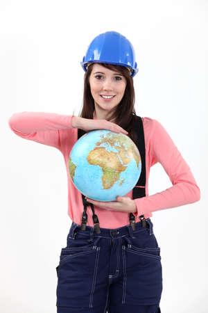 tradeswoman: Tradeswoman holding a globe Stock Photo