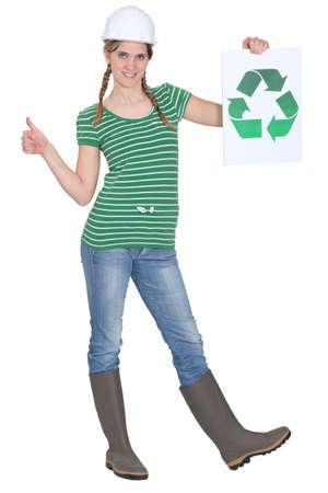obrero: Tradeswoman sosteniendo el símbolo de reciclaje