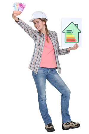 energy costs: Builder with a energy rating sign