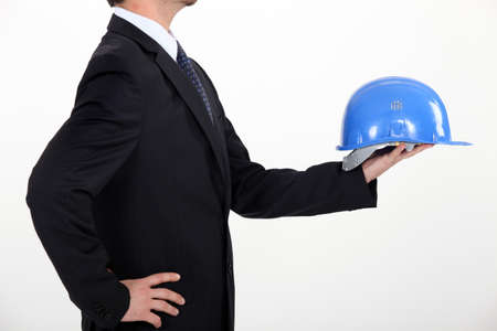 architect in profile holding out hard hat photo