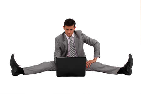 Businessman using his laptop with his legs spread apart photo