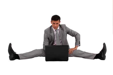 legs spread: Uomo d'affari con il suo computer portatile con le gambe divaricate Archivio Fotografico