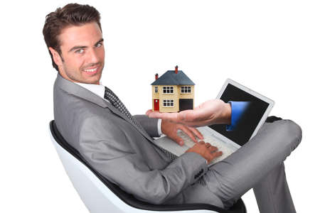 demanding: young man in grey suit sitting with laptop and hand sticking out of screen