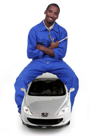 clutch cover: Mechanic sitting on a car and holding a lug wrench