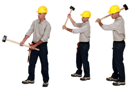 Three identical men hold sledge-hammers Stock Photo