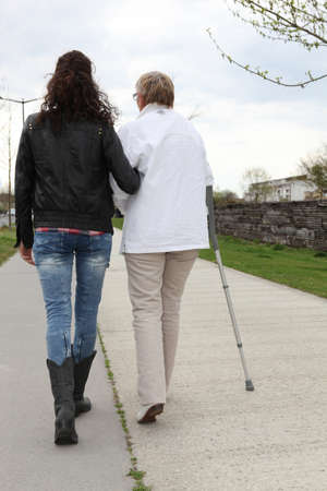 arthritic: Young woman helping elderly lady walk Stock Photo