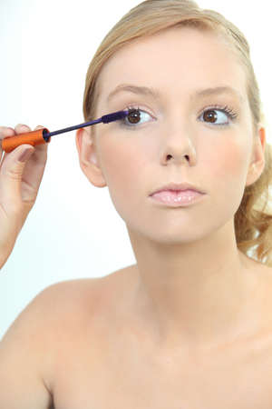 Young woman applying blue mascara photo
