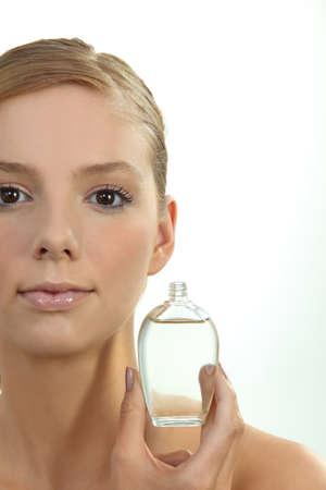 Blond woman holding perfume bottle