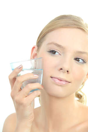 Blond woman holding glass of water to face photo