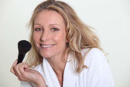 brush in: Woman in bathrobe holding make-up brush