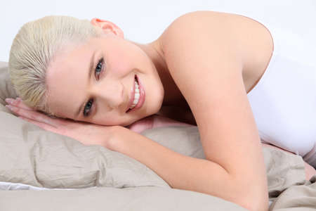 faced: Smiling young woman lying in bed