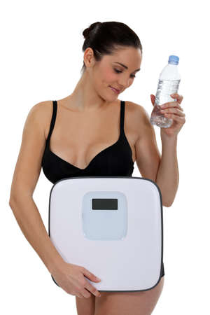kilos: Woman with bottle of water and scales Stock Photo