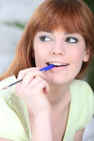 chew over: Young woman chewing on a pen Stock Photo