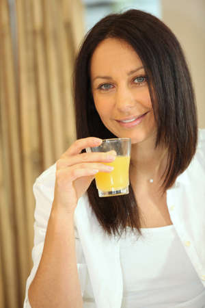 brunette woman drinking orange juice photo