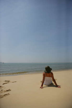 distant: Woman sat on a beach looking out at sea